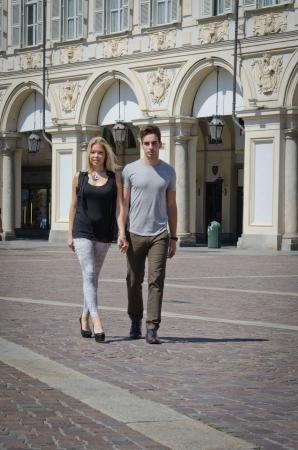 Outdoor shot of boyfriend and girlfriend walking in elegant, european city in the sun photo