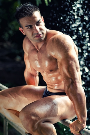 nipple piercing: Young muscle man sitting on railing and wet, looking to a side
