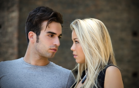brown haired: Attractive couple in love looking into each others eyes, blonde girl, brown haired guy, outdoors