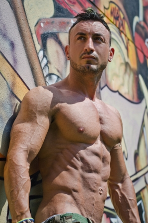 nipple man: Attractive muscle man outdoors against graffiti wall looking to a side Stock Photo