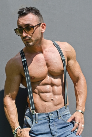 nipple piercing: Attractive bodybuilder shirtless with suspenders showing torso muscles, abs, pecs and arms