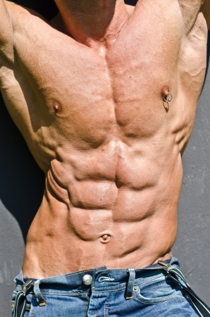 Bodybuilder torso with arms up, ripped abs and pecs with nipple piercing, wearing jeans photo