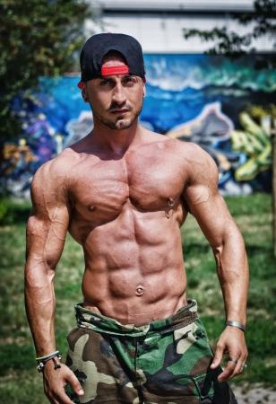 魅力的なボディービルダー胴の筋肉、abs、ペーチと腕を示す野球帽で上半身裸