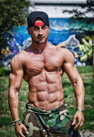 bodybuilder man: Attractive bodybuilder shirtless with baseball hat showing torso muscles, abs, pecs and arms