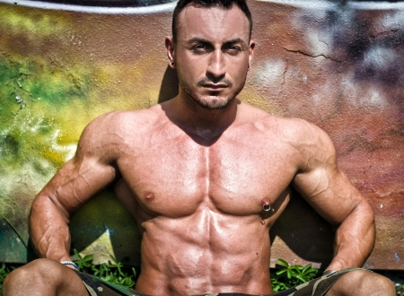nipple piercing: Muscular bodybuilder sitting against colorful wall showing ripped pecs and abs
