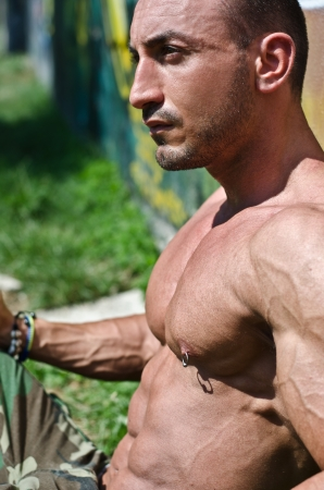 nipple piercing: Profile of attractive muscular bodybuilder shirtless sitting on the grass looking to a side