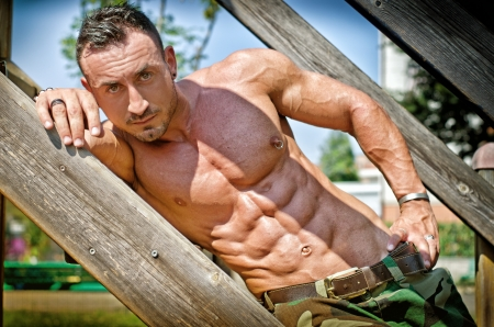 nipple piercing: Handsome, muscular bodybuilder laying on wood stairs in the sun showing bulging pecs and abs