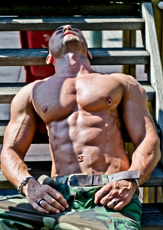Handsome, muscular bodybuilder laying on wood stairs in the sun showing bulging pecs and abs