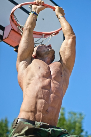Handsome, muscular bodybuilder hanging from basketball ring outdoors photo