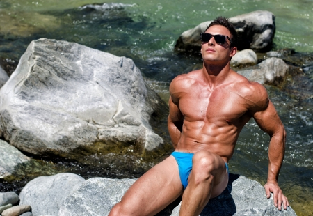 Young muscle man sitting on rock in river water, shirtless with sunglasses and swimming suit photo