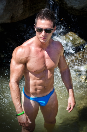 Attractive young muscle man standing in front of small waterfall in water pond photo
