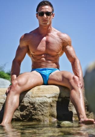 desnudo masculino: Hombre musculoso joven atractiva que se sienta en la roca al lado del agua, con gafas de sol