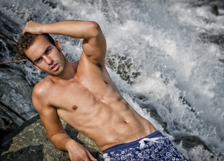 Attractive young man wearing a swimsuit near waterfall or river water photo