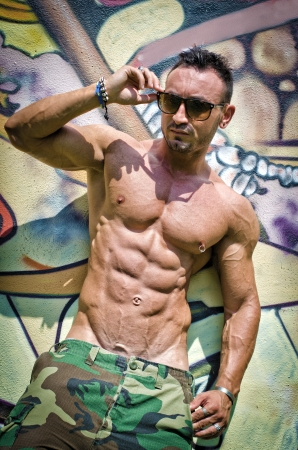 nipple piercing: Shirtless muscular young man against graffiti wall in the sun with sunglasses