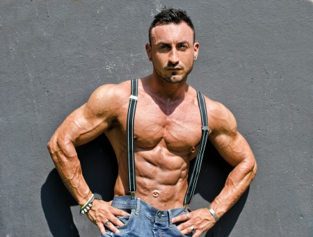 nipple piercing: Muscular bodybuilder shirtless with jeans and suspenders against grey wall Stock Photo