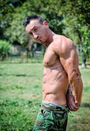 nipple piercing: Muscular bodybuilder doing triceps pose outdoors in a park, looking in camera