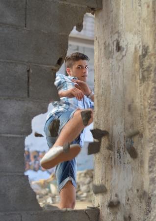 魅力的な若い男キックでレンガの壁を突破
