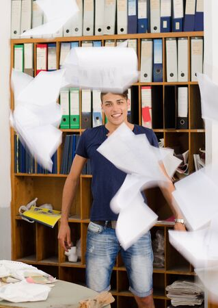 messed: Young man in very messy office with documents flying above him and messed up folders