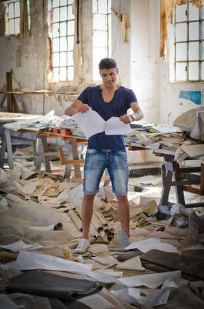 messy office: Attraente giovane uomo in ufficio disordinato o luogo di lavoro strappare fogli di carta