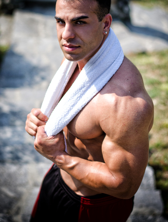 Very muscular bodybuilder outdoors holding towel around his neck photo