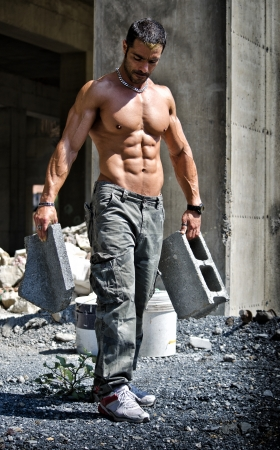 Sexy construction worker shirtless showing muscular body, holding big bricks photo