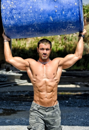 Hot, shirtless, muscular construction worker carrying big barrel over his head