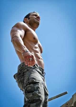 ホット、上半身裸、筋肉の建設労働者の上半身裸の青い空を背景に下から見られる