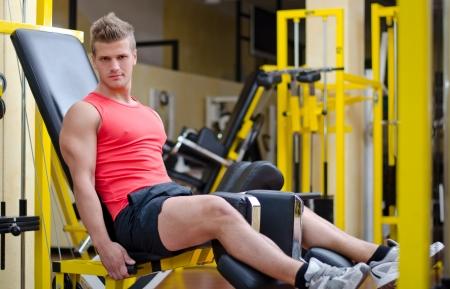 man working out: Apuesto joven haciendo ejercicio, ejercicio de piernas en aparatos de gimnasio