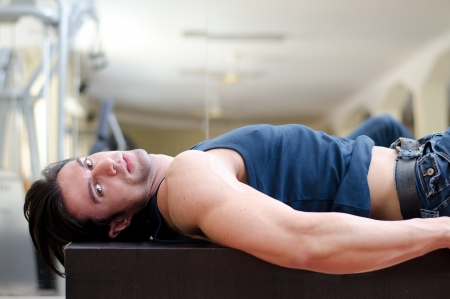 Handsome, sexy young man laying on his back, looking to a side, indoors in a gym photo