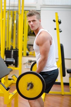 man working out: Hombre joven hermoso que se resuelve, en ejercicio de b�ceps con pesas en el gimnasio Foto de archivo