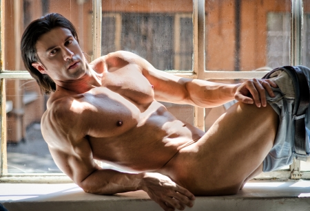 Half naked attractive and muscular young man laying down on a side by a window
