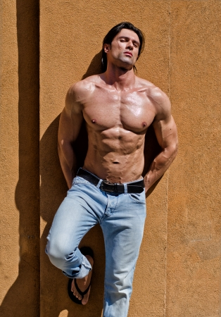 Attractive young man shirtless with jeans leaning against a wall with his eyes closed Stock Photo