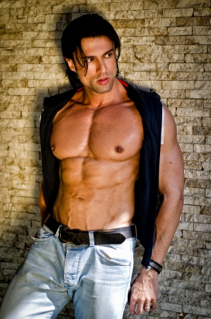 Attractive young man shirtless with jeans leaning against a wall looking to a side