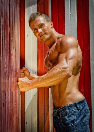 Handsome young man leaning against colorful beach changing rooms smiling. Naked muscular torso Stock Photo