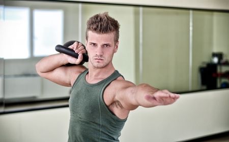 Attractive young man exercising with kettlebell, working out in gym photo