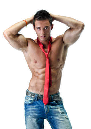 Attractive young muscle man shirtless, wearing only jeans and red necktie, isolated on white