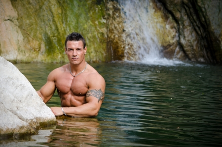 Handsome young muscle man standing in water pond, with waterfall behind