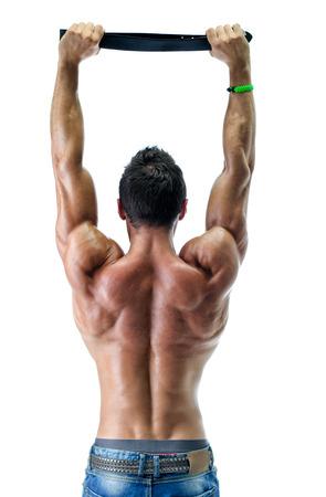 desnudo masculino: Hombre musculoso joven y atractiva est� de vuelta, jugando con el cintur�n negro, vistiendo pantalones vaqueros sin camisa, aislado en blanco