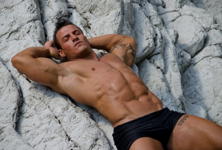 Attractive young man  laying shirtless on white rocks, eyes closed, wearing only black swimming suit