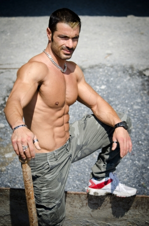 sexy construction worker: Sexy construction worker shirtless, showing muscular torso, abs and chest, outdoors