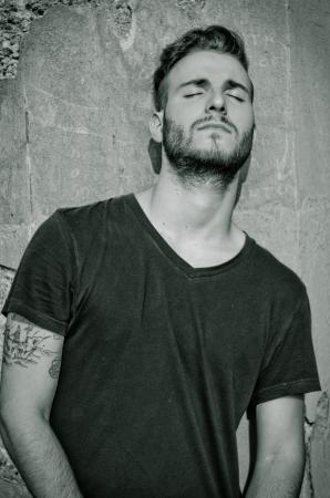 Aantrekkelijke jonge man met een zwart t-shirt, tegen ruwe muur, met de ogen gesloten