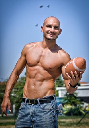 nudo maschile: Fit giovane uomo nudo con il calcio in mano, all'aperto sorridente Archivio Fotografico