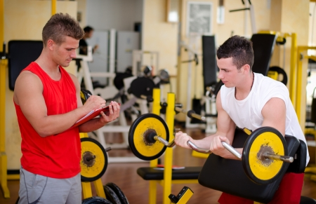 Personal trainer helping young male client in gym during workout on equipment Stock Photo