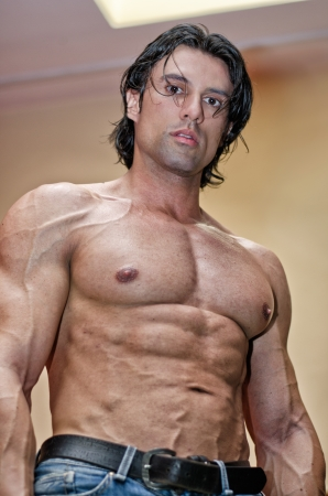 Attractive young muscle man showing muscular chest, abs and pecs, looking in camera Stock Photo