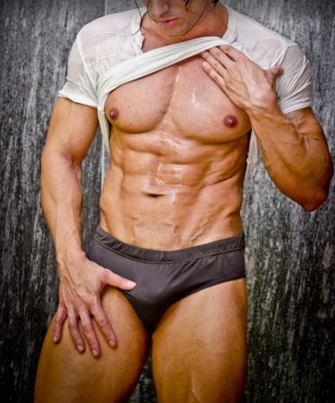 torso nudo: Sexy giovane uomo muscolare in una doccia indossando intimo scuro e t-shirt bianca bagnata Archivio Fotografico