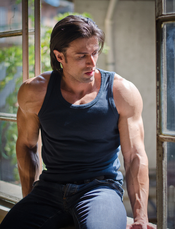 Attractive, muscular man sitting on open window looking down, wearing dark tanktop photo