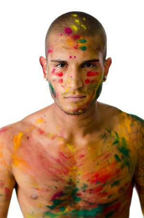 Handsome young man with skin all painted with colors and serious expression, looking in camera photo