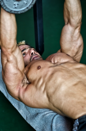 Muscular male bodybuilder working out on a bench in a gym photo
