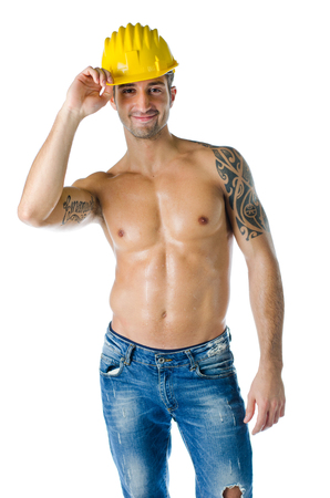 Smiling, muscular construction worker shirtless, wearing hard hat and jeans, isolated on white photo
