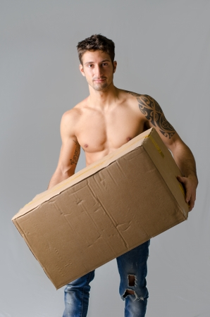 delivering: Handsome, athletic, shirtless young man carrying big cardboard box, isolated on grey background
